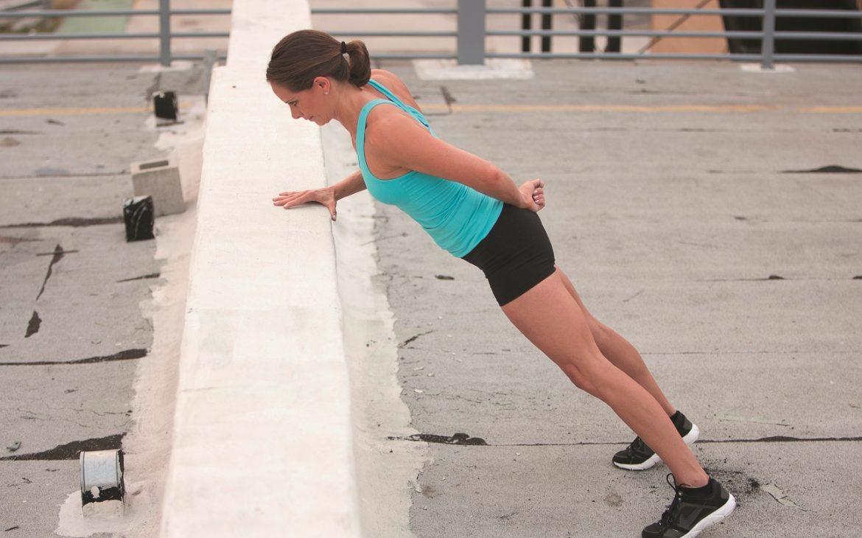 Trainierte Frau macht Druckübung draußen mithilfe einer Wand